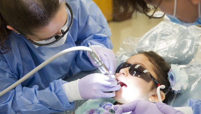 a dentist works on a child's teeth
