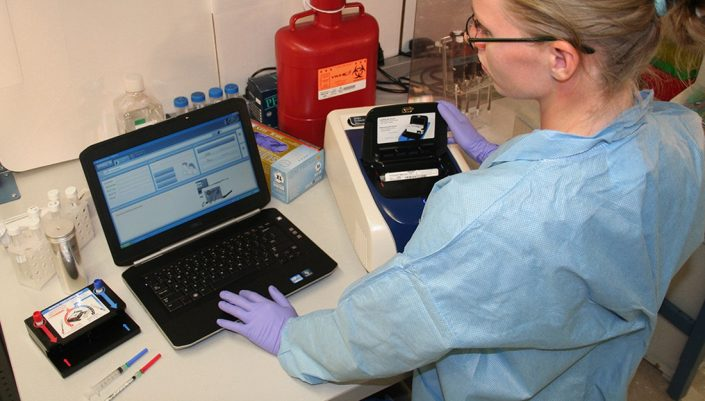 A lab scientist works with a diagnostic machine