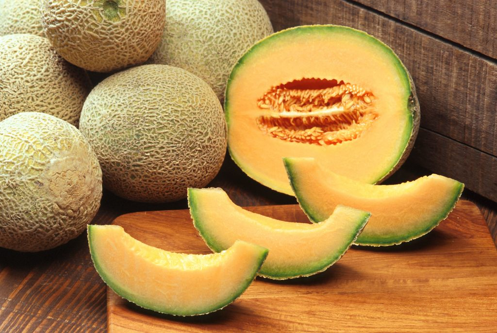 A cantaloupe sliced in half and sections, with six whole melons