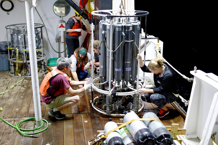 Scientists work with equipment designed to take water samples from ocean.