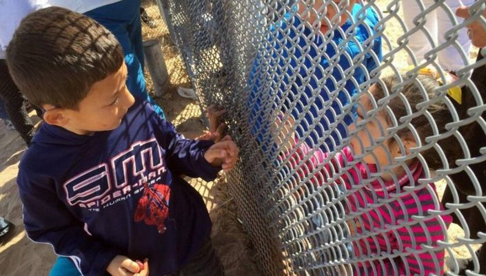 two boys look at each other through a hurricane fence