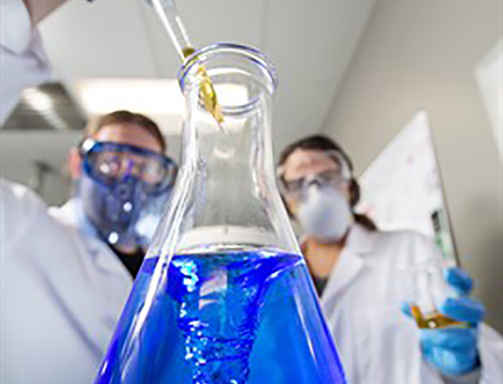 two scientists in lab masks work with a blue fluid