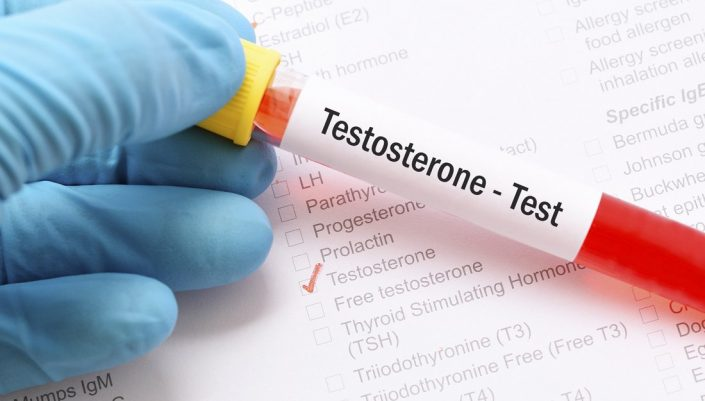 "two gloved hands holding a tube marked ""testosterone test"""
