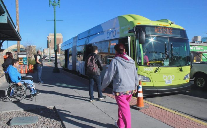 Pedestrians prepare to board a bus.