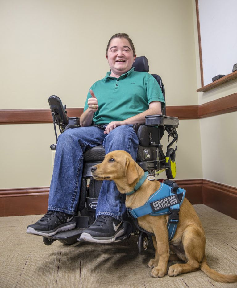 young man in wheelchair with service dog