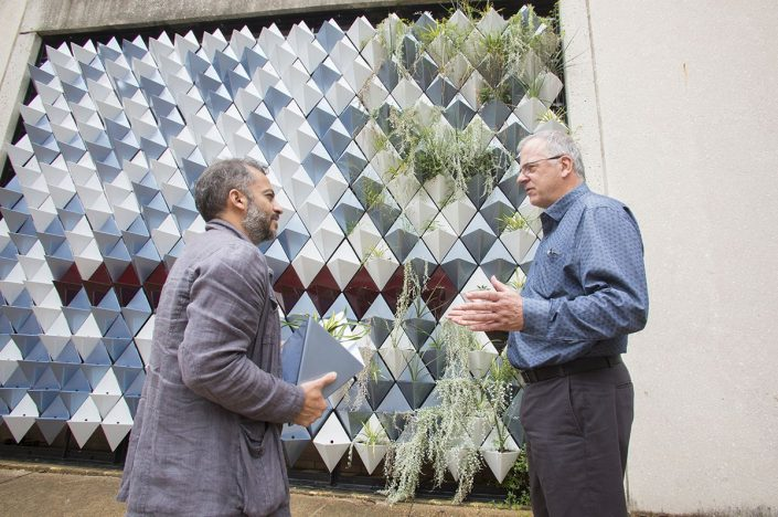 two men discuss plants to install in metal 'green wall'